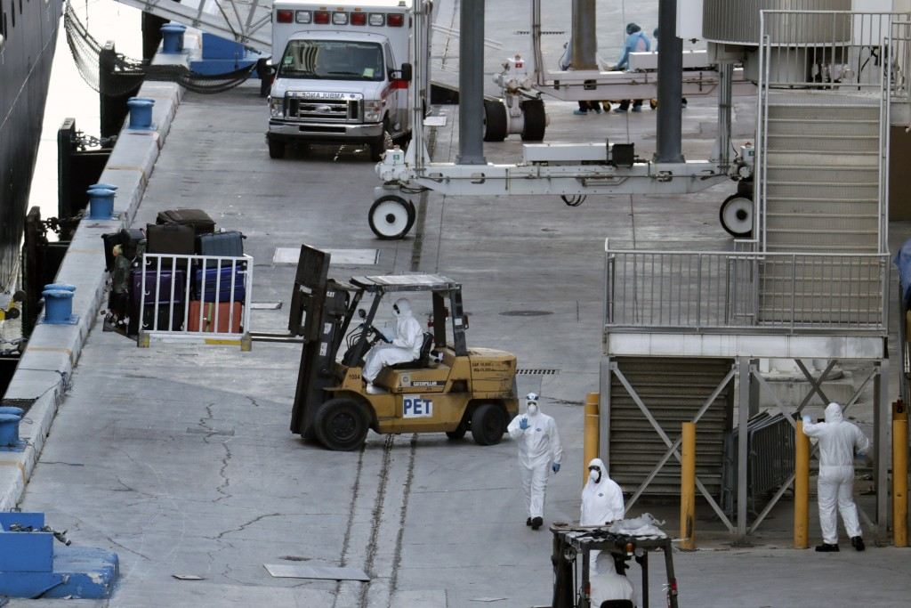 Workers in protective gear remove luggage form Carnavil's Holland America cruise ship Zaandam as it is docked at Port Everglades during the new corona...