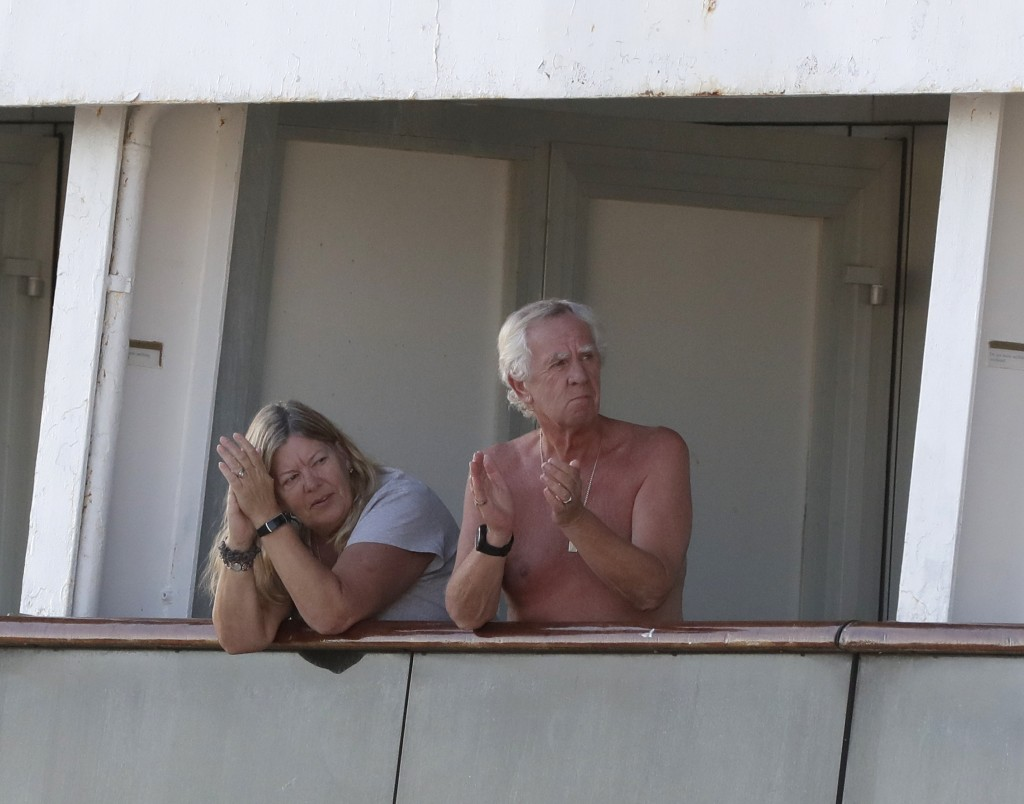 Passengers clap from their balcony after a crew announcement aboard the cruise ship Rotterdam as they wait to disembark at Port Everglades during the ...