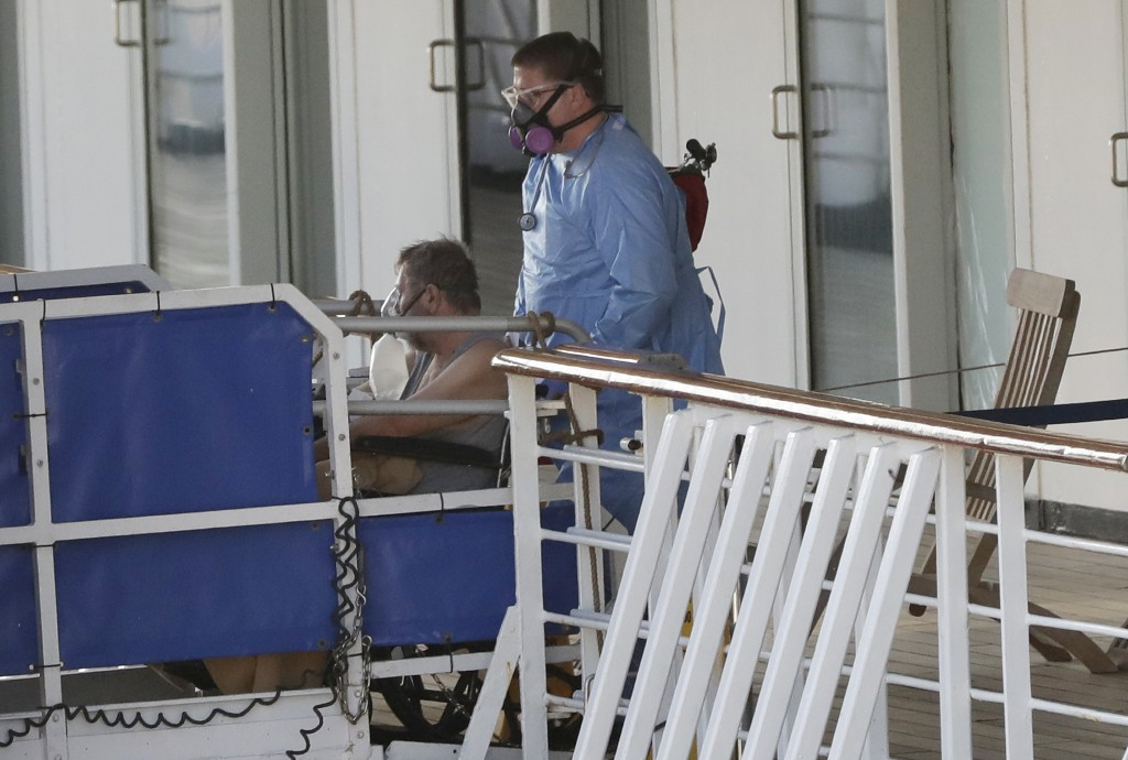 A person in a wheelchair is taken off the cruise ship Rotterdam at Port Everglades, Thursday, April 2, 2020, in Fort Lauderdale, Fla. A cruise ship th...