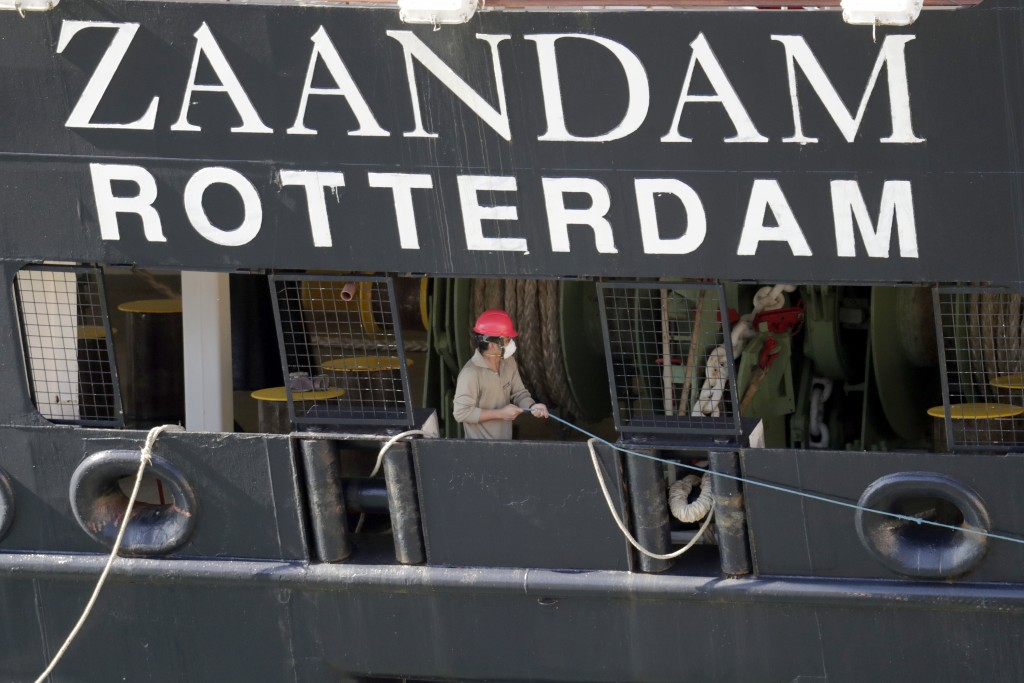 A crew member wearing a protective mask puts out lines as Carnaval's Holland America cruise ship Zaandam arrives at Port Everglades during the new cor...