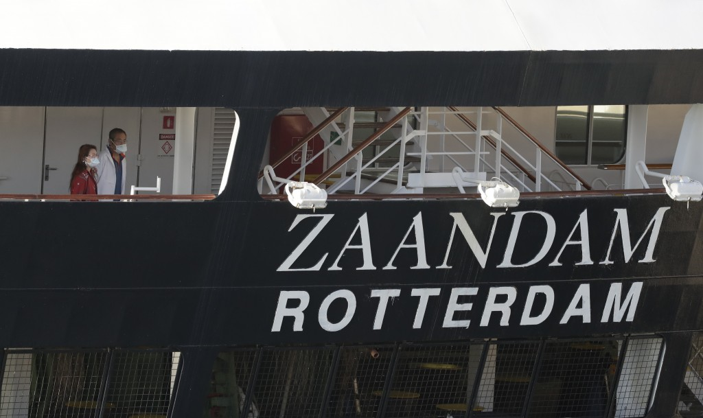 Two people look off the stern of the cruise ship Zaandam after it docked at Port Everglades during the new coronavirus pandemic, Thursday, April 2, 20...