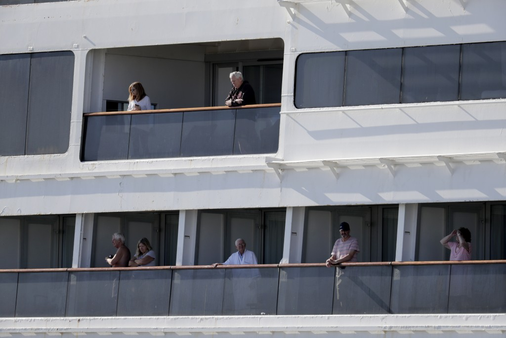 Passengers look out from Carnaval's Holland America cruise ship Rotterdam as it arrives at Port Everglades during the new coronavirus pandemic, Thursd...