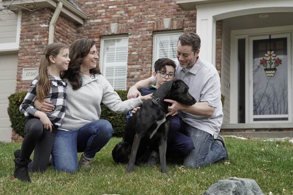 In this March 27, 2020, photo, Kim Simeon; her husband, Adam; and children, Annabel, 9, and Brennan, 11, pose for a photo with Nala, a dog they are fo...