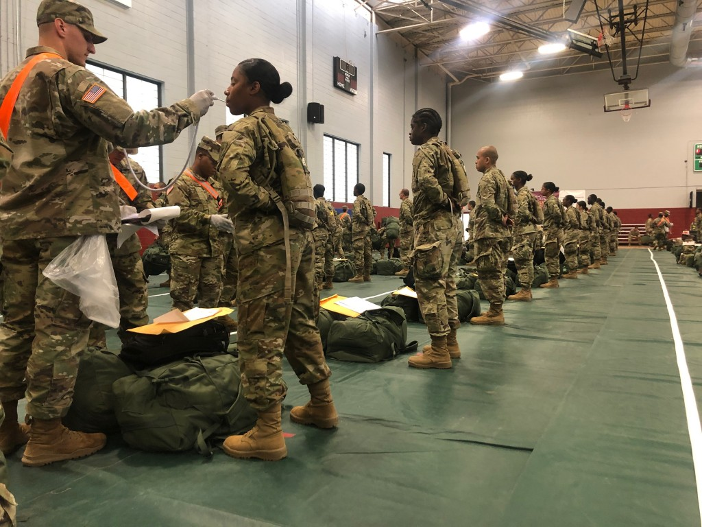 In this image provided by the U.S. Army, recent Army basic combat training graduates have their temperatures taken as they arrive at Fort Lee, Va, on ...