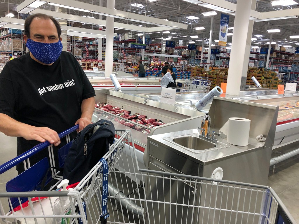 In this Tuesday, March 31, 2020, photo comedian Frank De Lima wears a mask and maintains social distancing while shopping at a Honolulu Sam's Club sto...