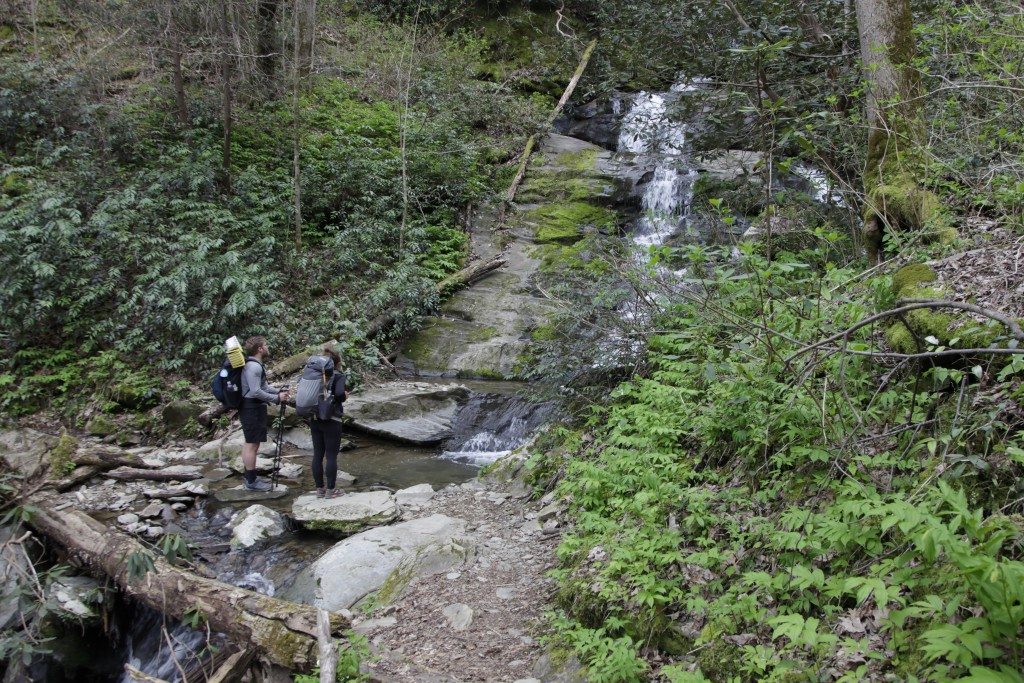 In this March 30, 2020, photo, Alexandra Eagle, right, and Jonathan Hall stand in front of a waterfall on the Appalachian Trail in Cosby, Tenn. The co...