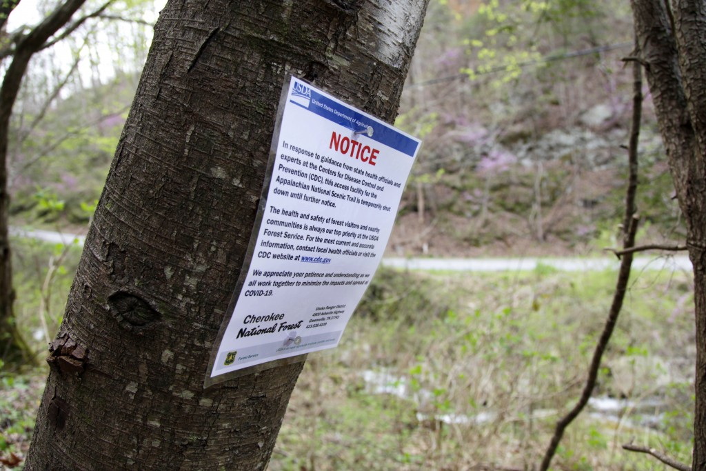 In this March 30, 2020, photo, a notice is nailed to a tree along a portion of the Appalachian Trail in Cosby, Tenn. Hikers have been asked to leave t...