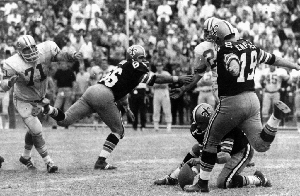 FILE - In this Nov. 8, 1970, file photo, New Orleans Saints' Tom Dempsey (19) moves up to kick a 63-yard field goal as teammate Joe Scarpati holds the...