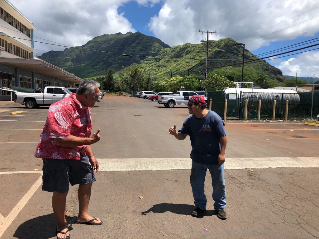 """In this Wednesday, April 1, 2020 photo Glen Kila, left, and Brad Suzuki, right, flash the Hawaii """"shaka"""" signs with their hands and give slight bows, ..."""