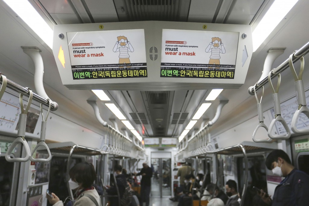 Electric screens about precautions against the COVID-19 illness are seen in a subway train in Seoul, South Korea, Monday, April 6, 2020. The new coron...