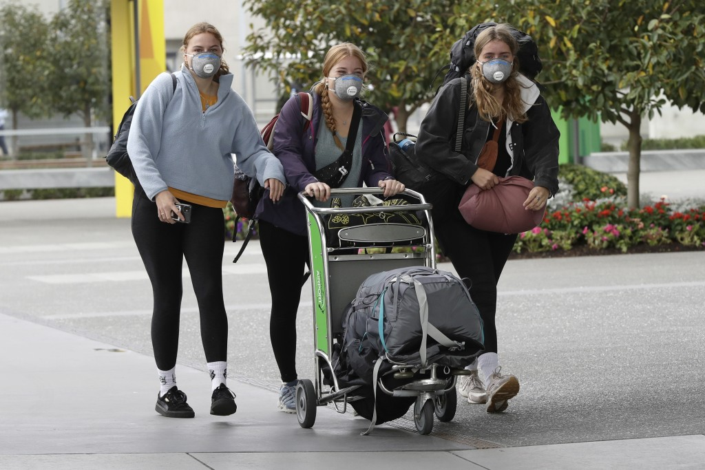 Foreign tourists arrive outside the Christchurch Airport terminal as they prepare to check in for a charter flight back to Germany via Vancouver from ...