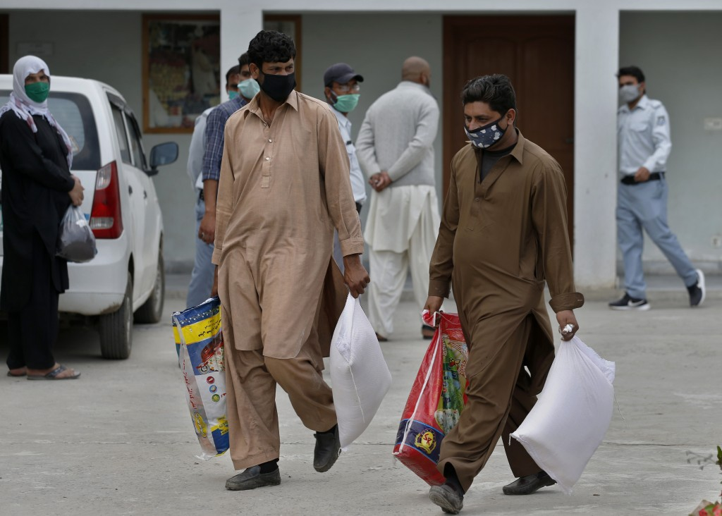 Daily wages workers carry sacks of wheat flour and other food supplies provided for free by a municipally, during a lockdown to try to contain the out...