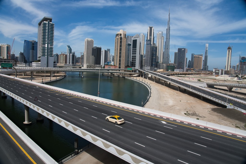A lone taxi cab drives over a typically gridlocked highway with the Burj Khalifa, the world's tallest building, in the skyline behind it in Dubai, Uni...