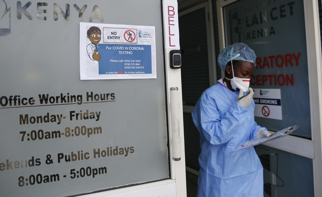 In this photo taken Sunday, April 5, 2020, laboratory technician Irene Ooko walks outside to take a nasal sample from a patient seeking a test for the...