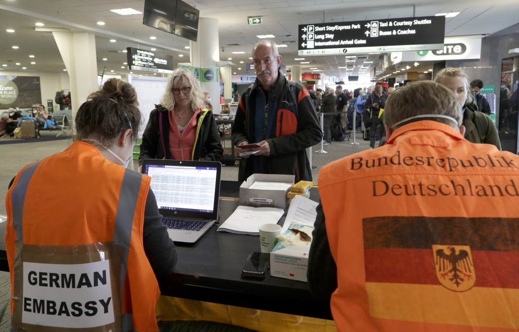 Foreign tourists wait to be checked by German Embassy staff at Christchurch Airport terminal as they prepare to check in for a charter flight back to ...