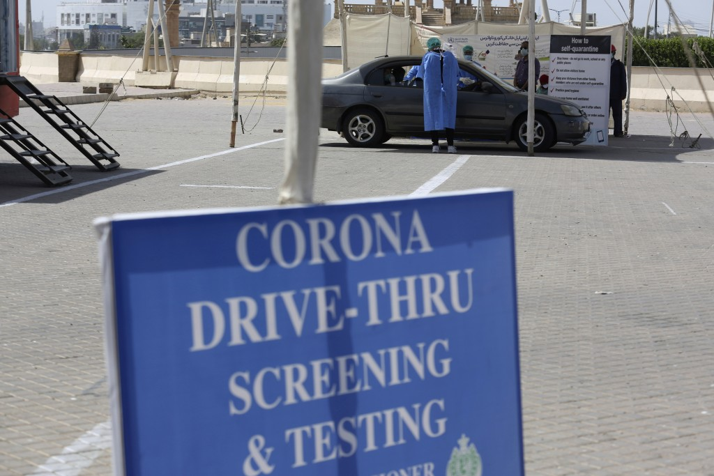 Health workers collect a specimen at a drive-thru testing and screening facility for the coronavirus, in Karachi, Pakistan, Monday, April 6, 2020. Aut...