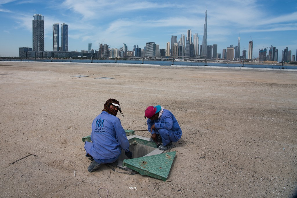 Two construction workers examine a drainage system with the Burj Khalifa, the world's tallest building, in the skyline behind them in Dubai, United Ar...