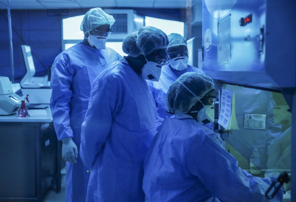In this photo taken Sunday, April 5, 2020, laboratory technicians, seen behind a blue-tinted window, work on testing patient samples for the new coron...