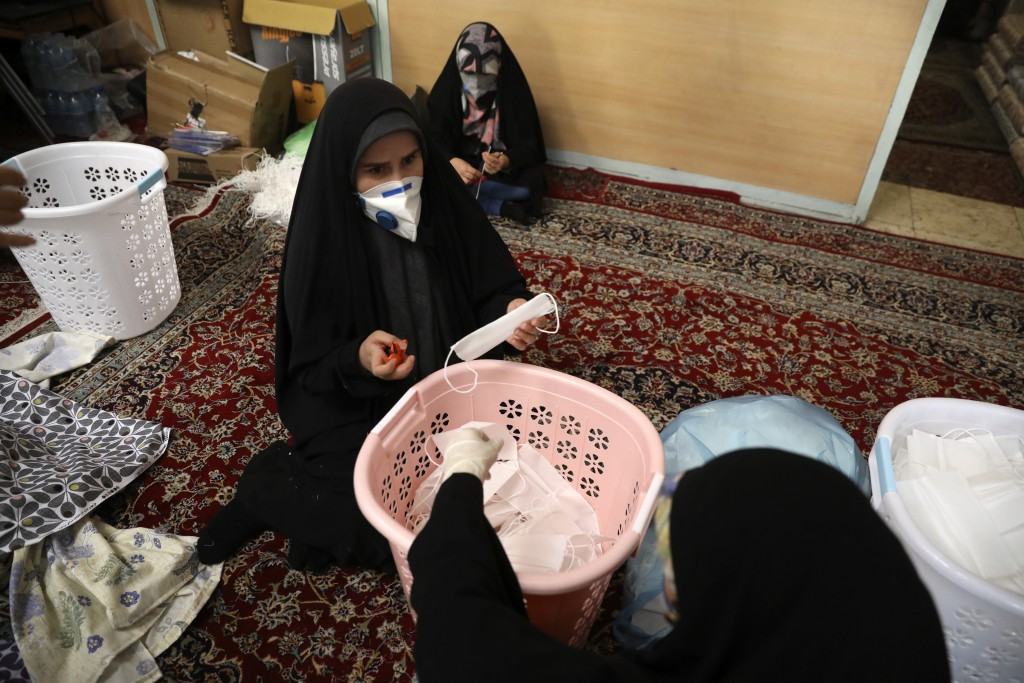 Volunteer women wearing face masks to curb the spread of the new coronavirus prepare face masks, in a mosque in southern Tehran, Iran, Sunday, April 5...