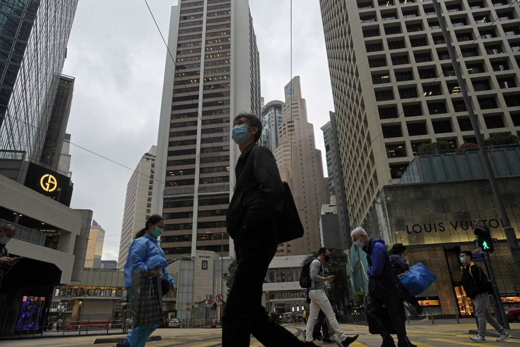 People wearing face masks walk at a downtown street in Hong Kong Monday, April 6, 2020. The new coronavirus causes mild or moderate symptoms for most ...