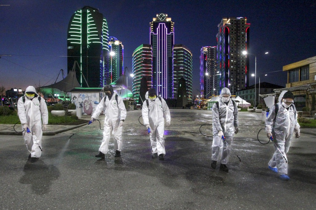 Municipal workers wearing protective suits spray disinfectant in an area in the center of Grozny, Russia, Monday, April 6, 2020. Ramzan Kadyrov, stron...