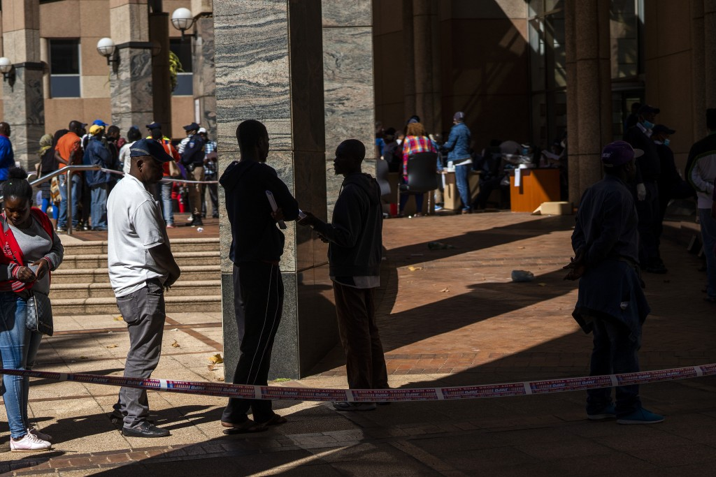 Informal vendors line up to receive temporary working licenses, at the entrance of a municipal office building, in Johannesburg,  Tuesday, April 7, 20...