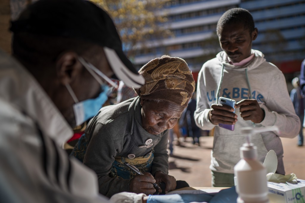 An informal vendor fills out paperwork to be granted a temporary working license, at the entrance of a municipal office building, in Johannesburg,  Tu...