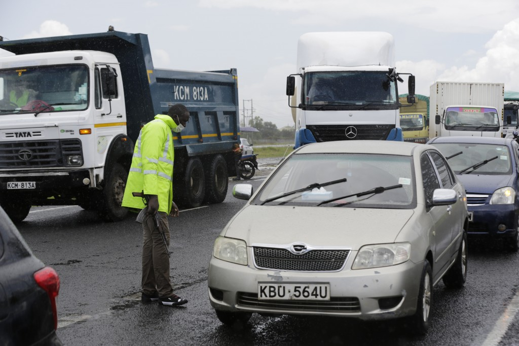 A Kenyan police officer at a road block along Mombasa Road stops vehicles traveling to Mombasa and Machakos, in Nairobi, Kenya, Tuesday, April 7, 2020...
