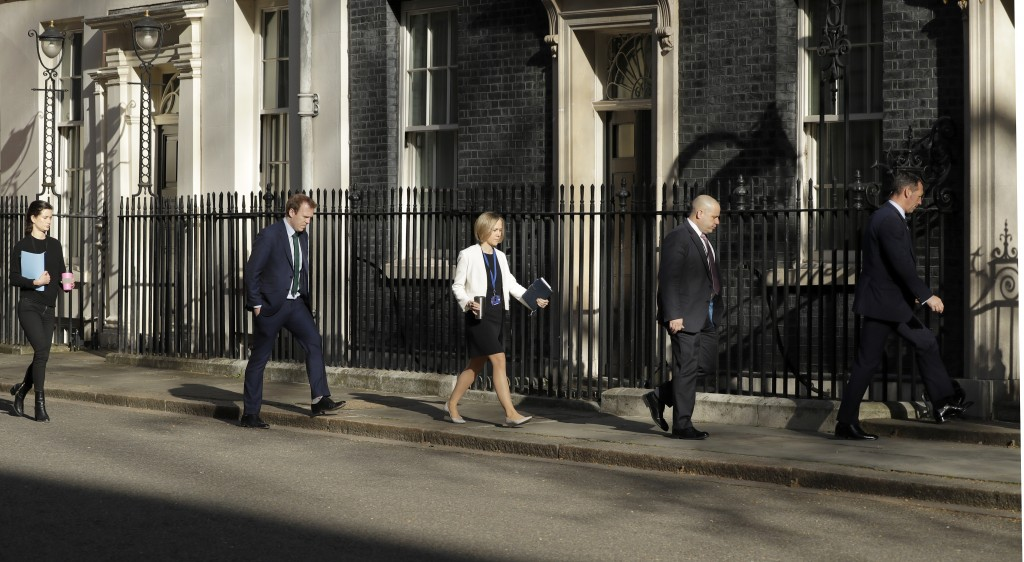 Members of a meeting keep their distance as they arrive at 10 Downing Street as British Prime Minister Boris Johnson was moved to intensive care after...