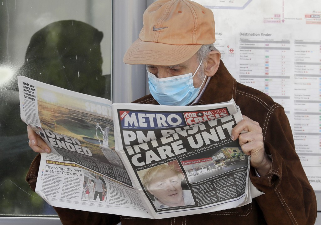 A man reads a newspaper with the headline: 'PM in intensive care', outside St Thomas' Hospital in central London as British Prime Minister Boris Johns...