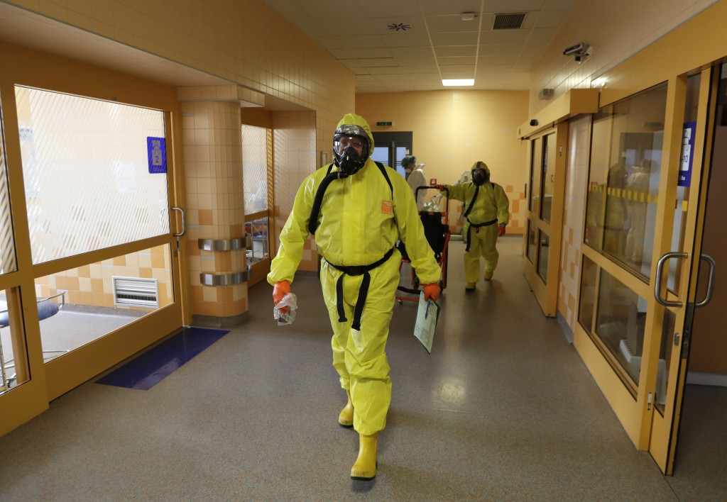 Paramedics in protective gear walk through an intensive care unit (ICU) after bringing in a new COVID-19 patient into the General University Hospital ...