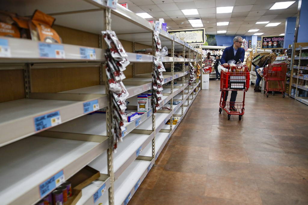 FILE - In this Friday, March 13, 2020 file photo, shoppers browse empty shelves at a supermarket in Larchmont, N.Y,  amid panic-buying due to the coro...