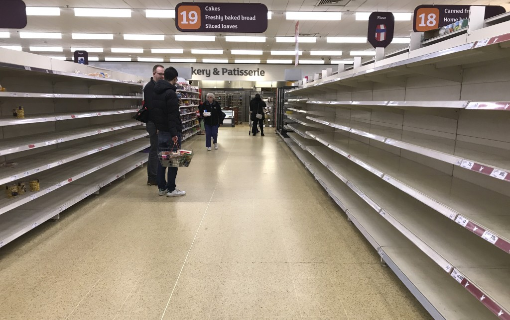 FILE - In this Thursday, March 19, 2020 file photo, people stand in an aisle of empty shelves in a supermarket in London,  amid panic-buying due to th...