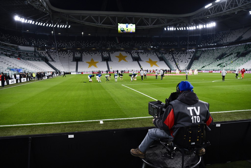 FILE - In this Sunday, March 8, 2020. filer, players warm up in the empty Allianz stadium, prior to the Serie A soccer match between Juventus and Inte...