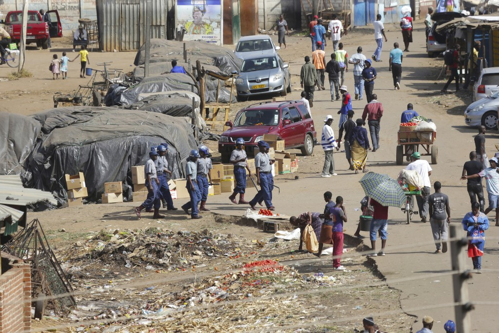 Zimbabwe riot police patrol the streets near a fruit and vegetable market full of people despite a lockdown in an effort to curb the spread of the cor...