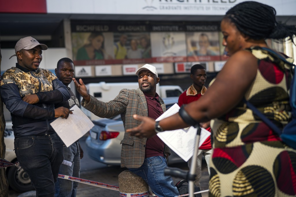 Informal vendors refused temporary working licenses speak to each other,  in Johannesburg Tuesday, April 7, 2020. South Africa and more than half of A...