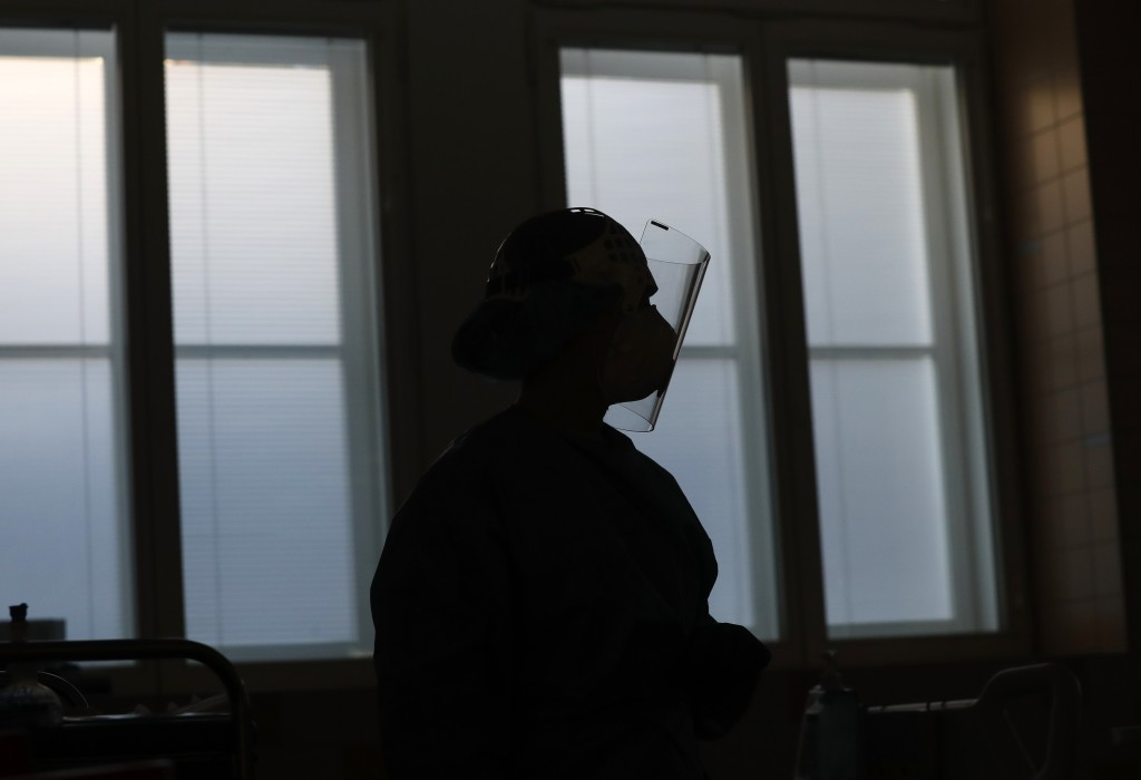 A healthcare worker is silhouetted against the window during a shift in an intensive care unit (ICU) at the General University Hospital where patients...