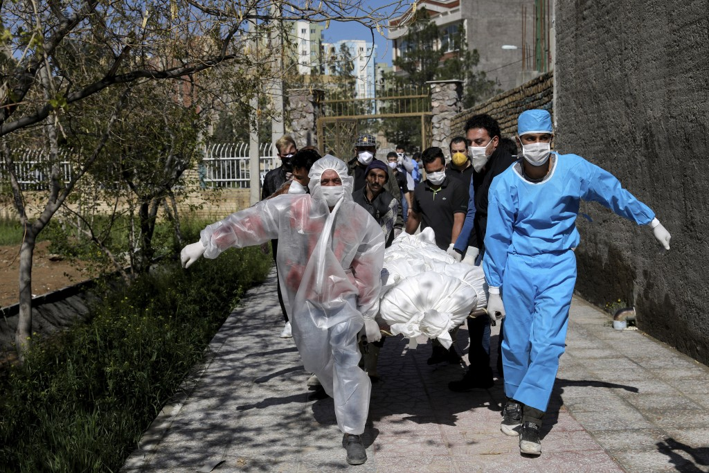 FILE - In this Monday, March 30, 2020 file photo, people carry the body of a victim who died after being infected with the new coronavirus at a cemete...