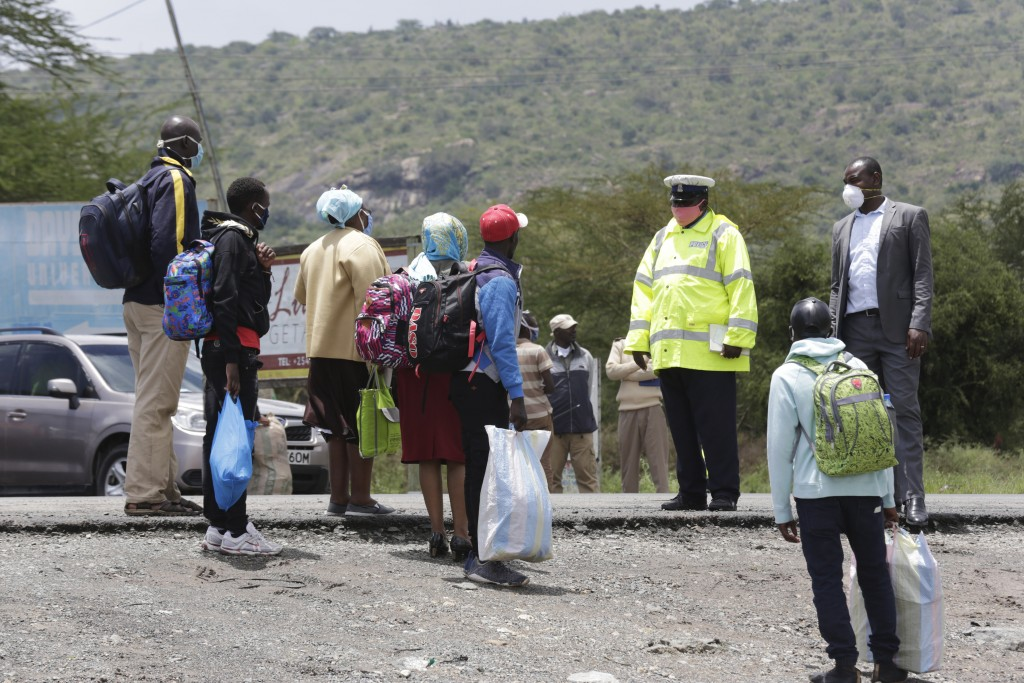 A Kenyan police officer speaks to people at a road block along Mombasa Road after vehicles traveling to Mombasa and Machakos were turned away, in Nair...