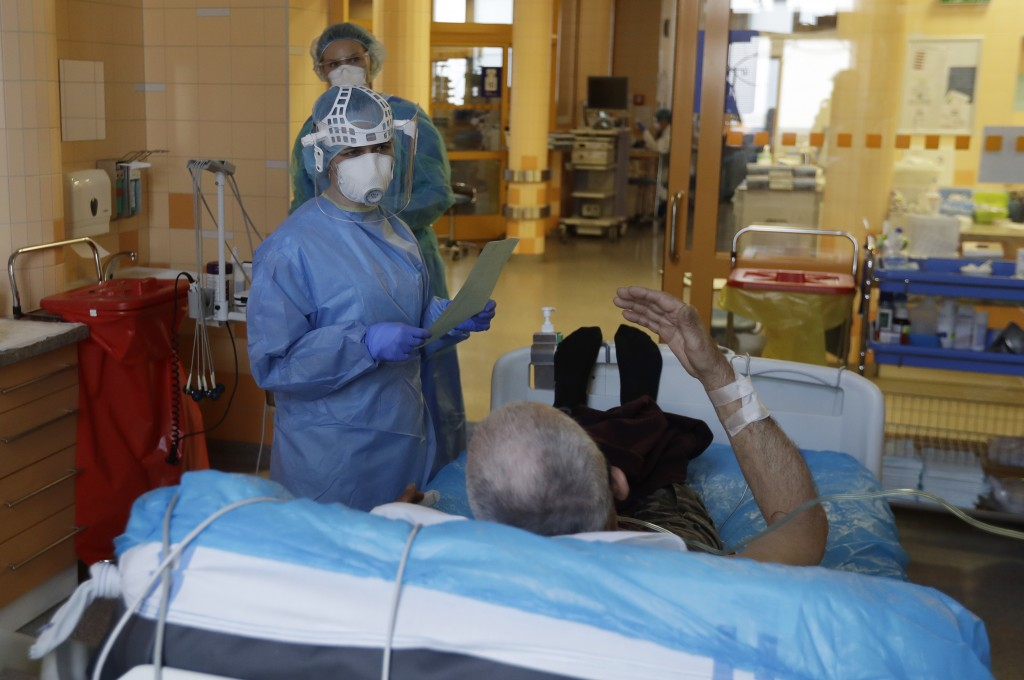 Healthcare workers attend to a newly admitted COVID-19 patient in an intensive care unit (ICU) at the General University Hospital in Prague, Czech Rep...