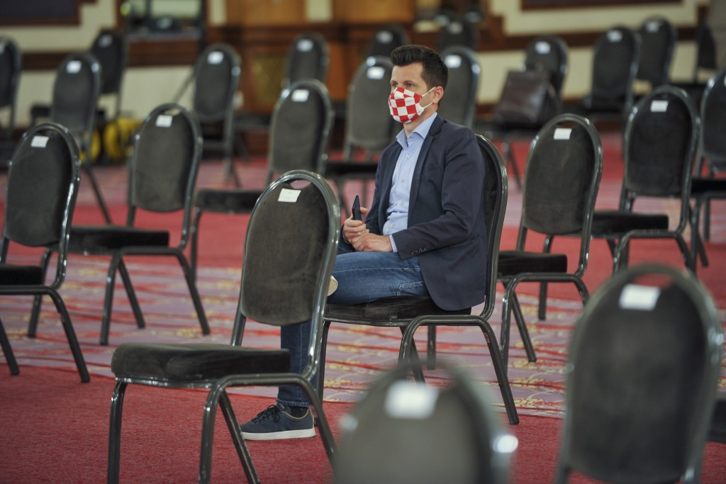 A Croatian parliament member wearing a mask with national colors attends a session at a hotel in Zagreb, Tuesday, April 7, 2020. Croatian lawmakers ha...
