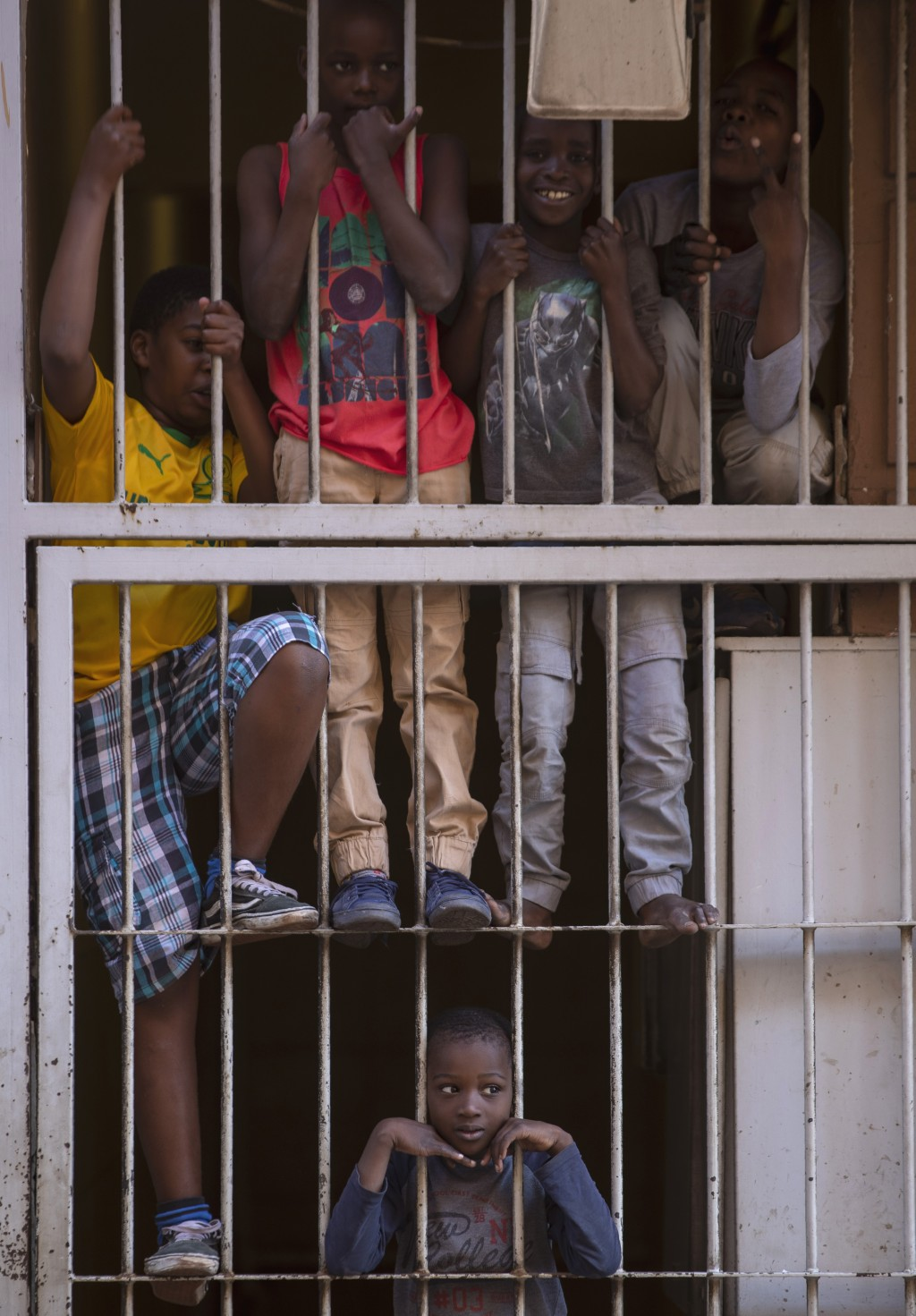 Children look out from a security gate of their flat, during a lockdown to help curb the spread of the new coronavirus in Johannesburg, South Africa, ...