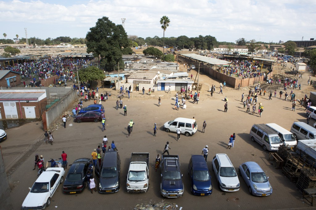 Hundreds of people buy goods at a fruit and vegetable market, despite a lockdown in an effort to curb the spread of the coronavirus,  in Harare, Zimba...