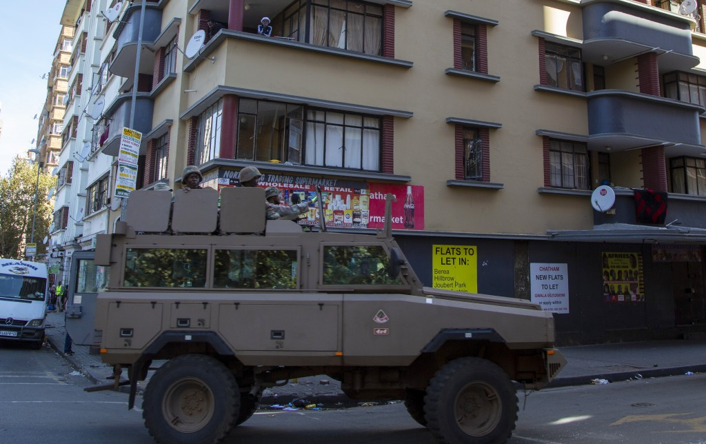 Residents stand on a balcony as a South African National Defence Forces vehicle patrol the street, in Johannesburg, South Africa, Tuesday, April 7, 20...
