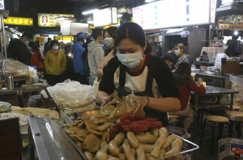A vendor wears face mask to help curb the spread of the coronavirus and waits for customers at a night market in Taipei, Taiwan, Wednesday, April 8, 2...
