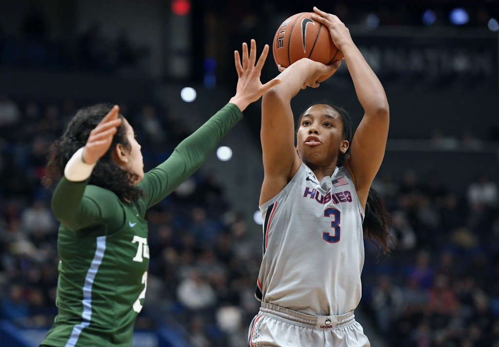 FILE - In this Wednesday, Feb. 19, 2020, file photo, Connecticut's Megan Walker, right, shoots over Tulane's Irina Parau in the second half of an NCAA...