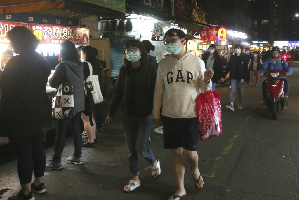People wear face masks to help curb the spread of the coronavirus and visit at a night market in Taipei, Taiwan, Wednesday, April 8, 2020. The new cor...