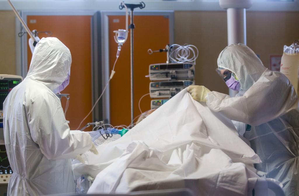 FILE - In this March 25, 2020 file photo, medical staff tend to patients at the intensive care unit of the Casalpalocco COVID-19 Clinic on the outskir...