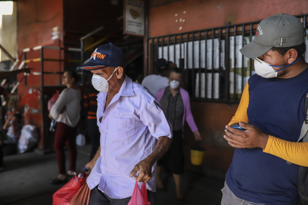 Passengers wearing masks to protect against the spread of the new coronavirus, get ready to board a bus at the Mayoreo market in Managua, Nicaragua, T...