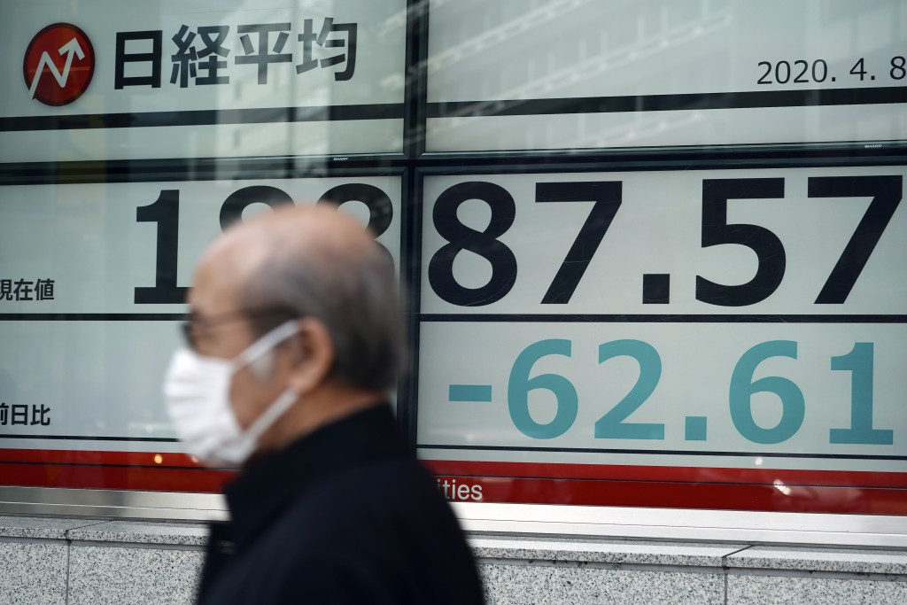 A man with a protective mask walks past an electronic stock board showing Japan's Nikkei 225 index at a securities firm Wednesday, April 8, 2020, in T...